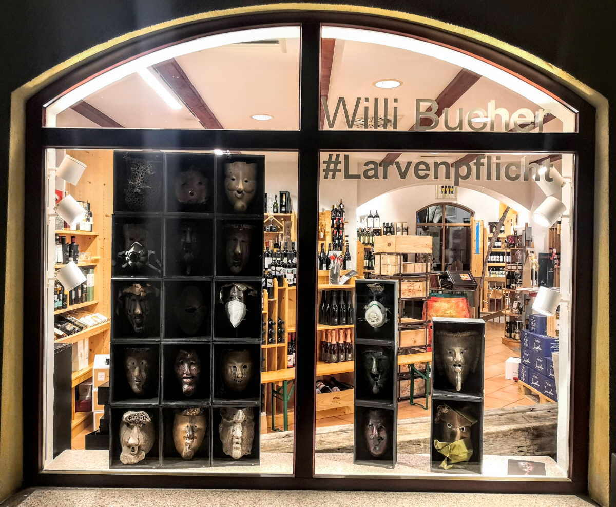 Willi Buchers Larven - auch teils mit Mundmasken - sind jetzt im Schaufenster der Bacchus Vinothek ausgestellt. Foto: pm