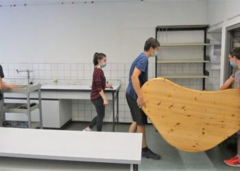 Alles muss raus: Schülerinnen und Schüler schaffen die Möbel aus dem Physikraum in ein  leeres Klassenzimmer