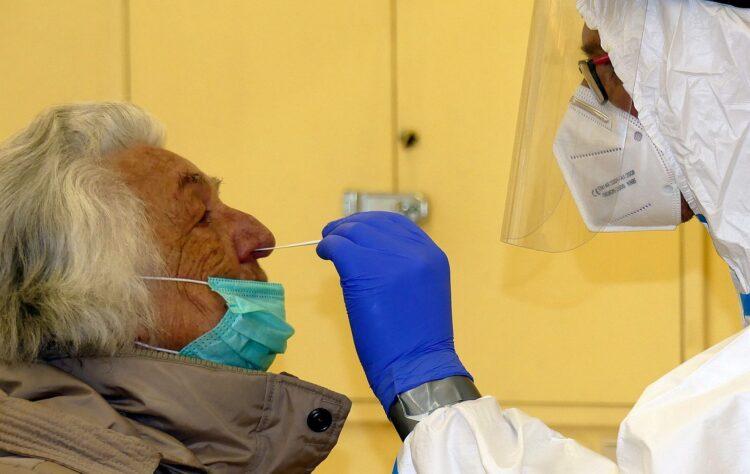 Im Testzentrum: Ein DRK-Mitarbeiter führt das Teststäbchen in die Nase einer älteren Dame ein. Foto: him