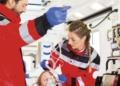 Zwei Rettungssanitäter, eine Frau und ein Mann, helfen und versorgen einer verletzte Frau in einen Rettungswagen. Foto: pm
