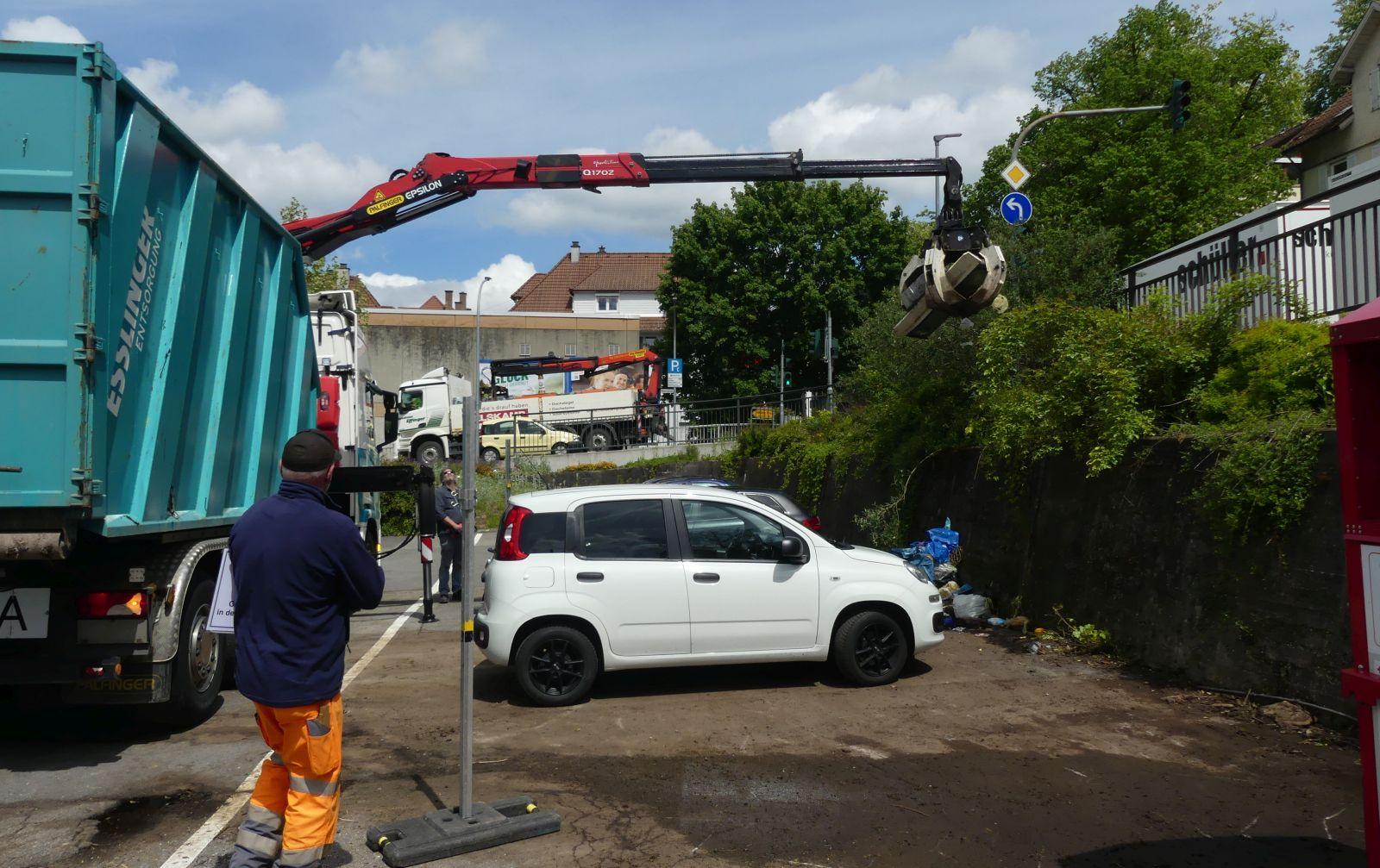 Mit einem Kran lädt ein Müllwerker den Restmnüll vom Schweizer-Parkplatz in den Container. Fotos: him