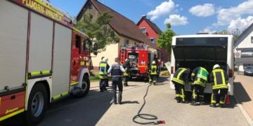 Feuerwehrleute inspizieren den Busmotor Foto: emo