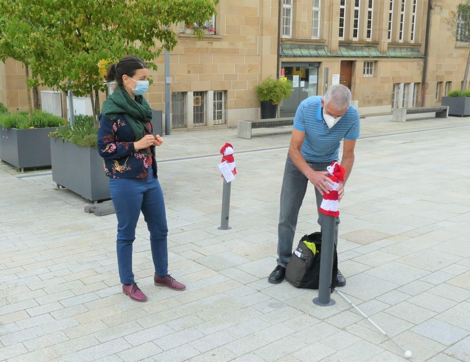Anselm Schmid zieht einem Poller am Rathausplatz ein rot-weißes Mützchen über: Oberbürgermeisterin Dorothee Eisenlohr schaut zu. Fotos: him