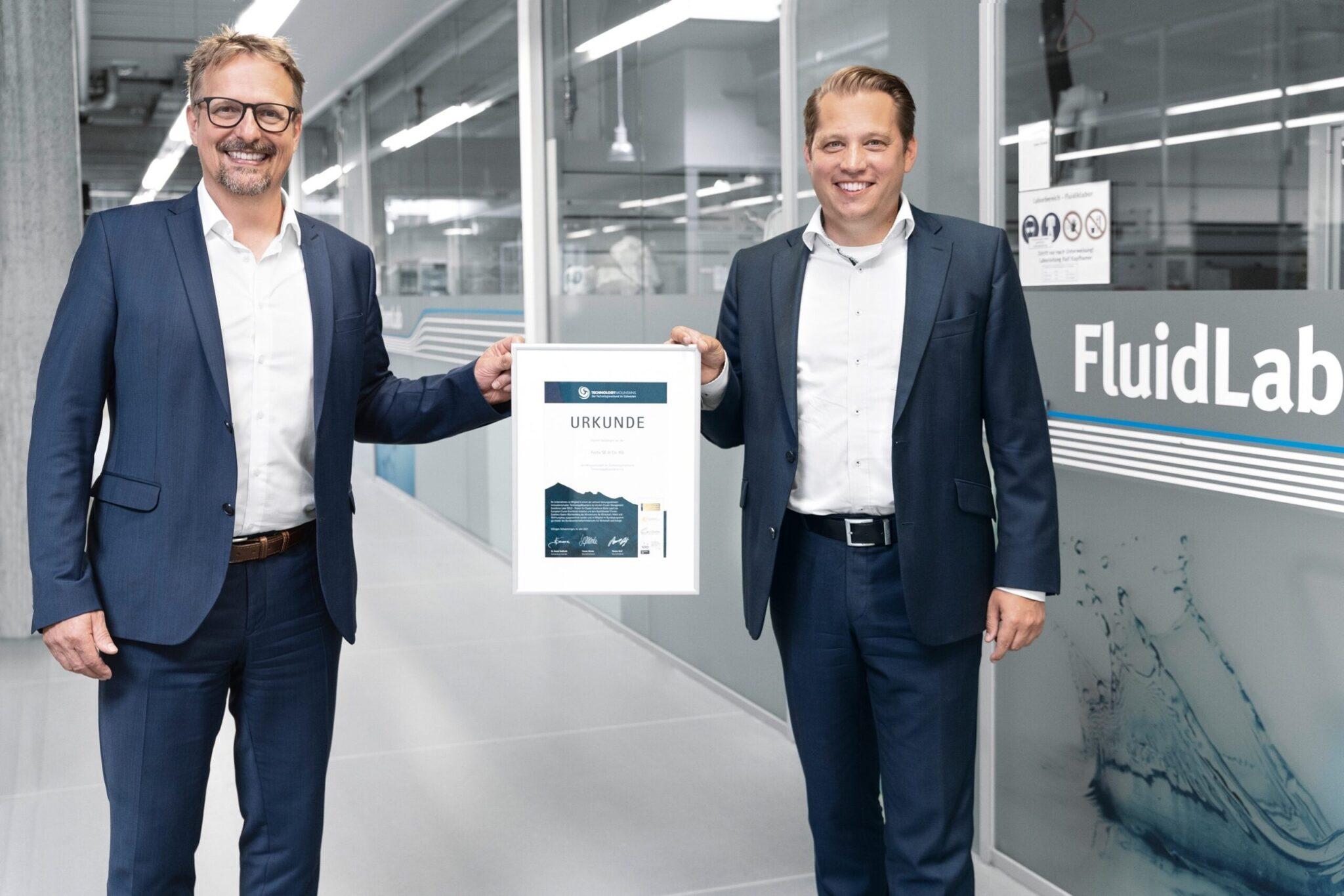Prof. Dr. Volker Nestle, Entwicklungsleiter LifeTech bei Festo (links), und Dr. Frank Jacob, Leiter des Geschäftsbereichs LifeTech bei Festo, halten die Urkunde in Händen. Foto: Festo