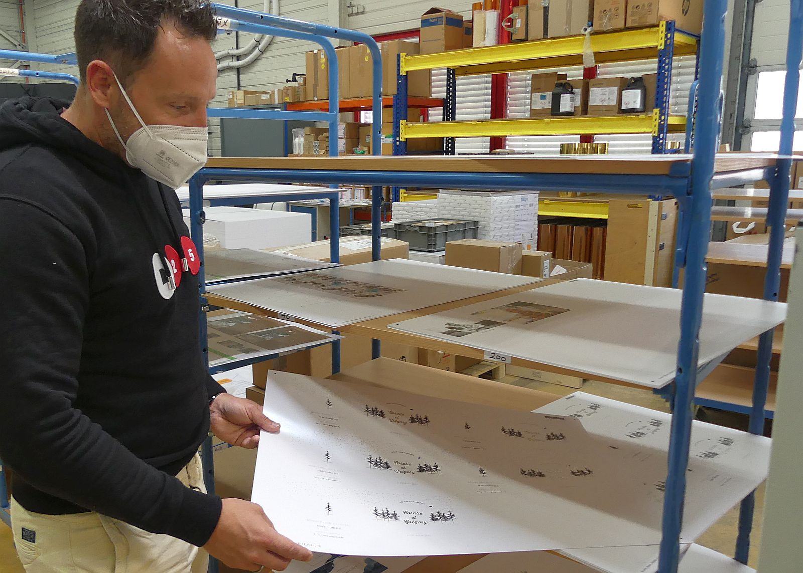 Patrick Leibold mit einem Papierbogen mit frisch gedruckten Einladungskarten.