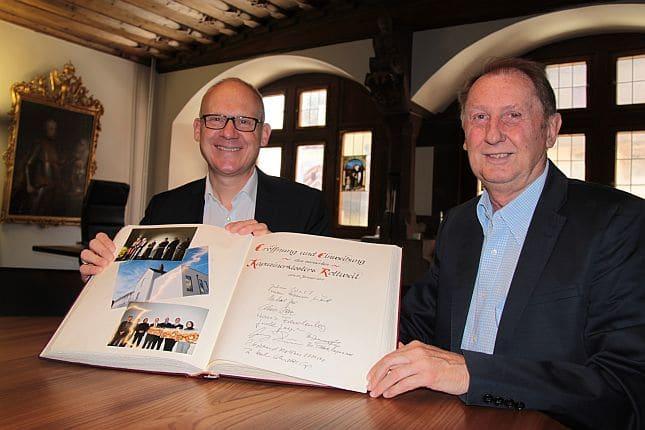 Rainer Müller (rechts), hier mit Oberbürgermeister Ralf Broß und dem Goldenen Buch der Stadt Rottweil. Foto:  Stadt Rottweil